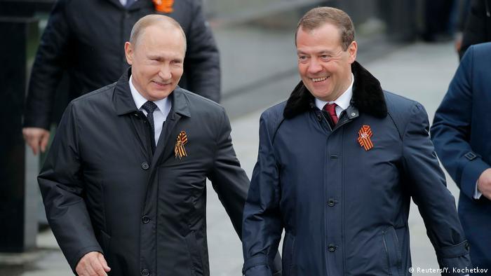 Russian President Vladimir Putin and Prime Minister Dmitry Medvedev smiling