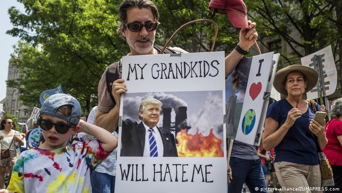 A climate protester holds a sign showing Donald Trump in front of a coal factory