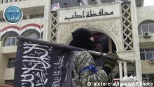 ARCHIV 2015*****FILE - In this file photo posted on the Twitter page of Syria's al-Qaida-linked Nusra Front on March 28, 2015, which is consistent with AP reporting, a fighter from Syria's al-Qaida-linked Nusra Front holds his group flag as he stands in front of the governor building in Idlib province, north Syria. Clashes between two extremist factions in northwestern Syria have left dozens of fighters dead on both sides and raised fears of more deadly violence between groups battling President Bashar Assad's troops ahead of U.N.-brokered peace talks later this month. (Al-Nusra Front Twitter page via AP, File) |