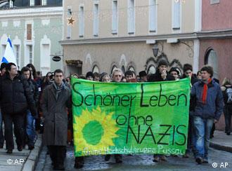 Demonstrators holding a green banner that reads A beautfiul life without Nazis