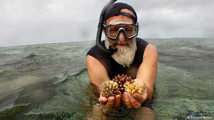 Man with snorkel holds corals