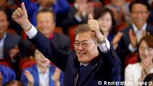 09.05.2017 Moon Jae-in, the presidential candidate of the Democratic Party of Korea, poses for photographs as he watches a television report on an exit poll of the presidential election in Seoul, South Korea May 9, 2017. REUTERS/Kim Hong-Ji