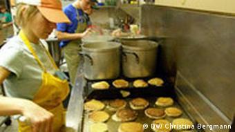 Eine junge Frau und ein junger Mann bereiten in einer Großküche Pancakes und Würstchen zu (Quelle DW/Christina Bergmann)