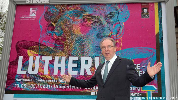 Reiner Haseloff in front of Luther poster (Photo: picture alliance/dpa/P. Förster)