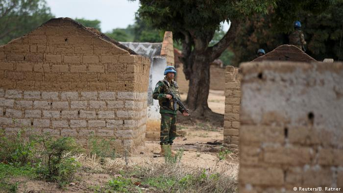 An armed soldier belonging to the UN mission is standing between two destroyed houses