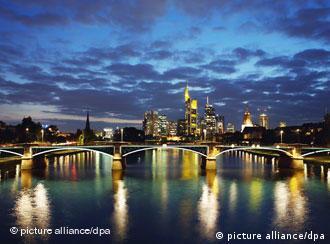 Die beleuchtete Ignatz-Bubis-Brücke spiegelt sich im Main, dahinter ragen die Hochhäuser der Banken und Konzernzentralen in den Himmel von Frankfurt (Foto: dpa)