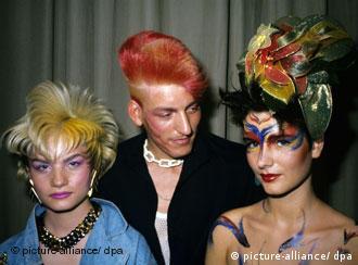 Zwei Frauen und ein Mann, mit sehr bunten, hoch stehenden Frisuren