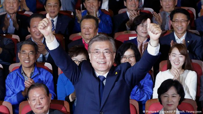 South Korean President Moon Jae-in raises his hands
