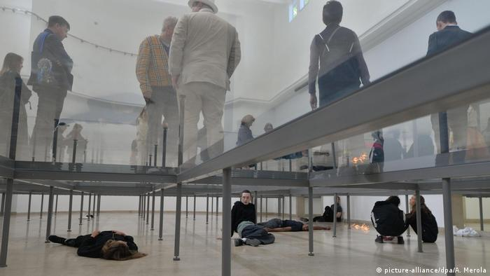 People standing on beams and lying on the floor in an installation