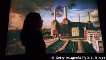 A member of staff poses in front of a picture featured in the album 'Animals' showing a pig floating between two chimneys of the Battersea Power Station and which was conceived by Roger Waters and designed by long-time collaborator, Storm Thorgerson of Hipgnosis, during a photocall at the 'The Pink Floyd Exhibition: Their Mortal Remains' at the Victoria and Albert Museum in west London on May 9, 2017. / AFP PHOTO / Daniel LEAL-OLIVAS / RESTRICTED TO EDITORIAL USE (Photo credit should read DANIEL LEAL-OLIVAS/AFP/Getty Images)