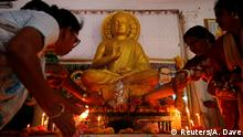 People light candles in front of a statue of Lord Buddha inside a temple on the occasion of Buddha Purnima festival, also known as Vesak day, in Ahmedabad, India, May 10, 2017. REUTERS/Amit Dave