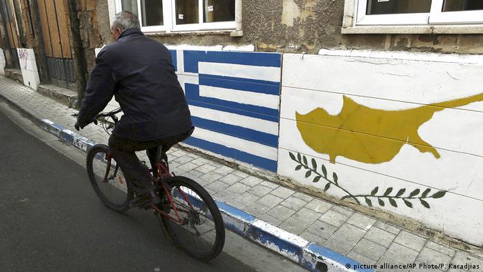 Мужчина едет на велосипеде мимо флагов Греции и Республики Кипр