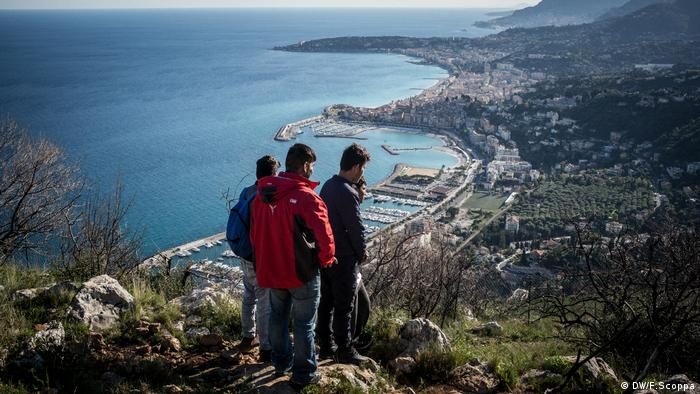 On top of a hill, four young men survey the route down to Menton.