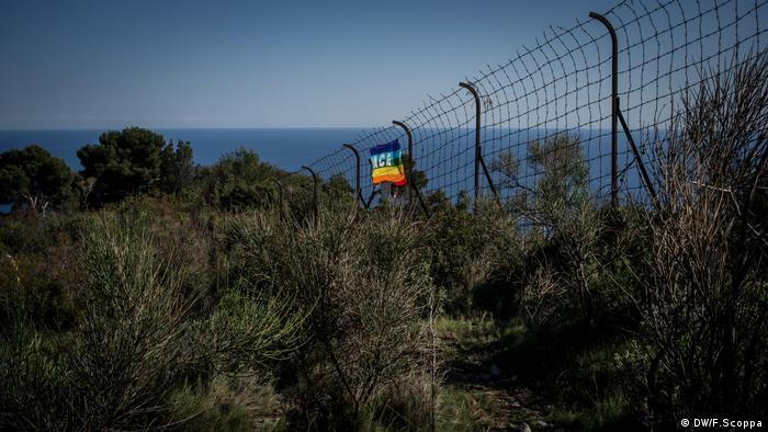 A pace flag hanging from the border fence between Italy and France