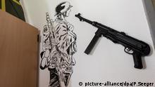 ARCHIV - Im Aufenthaltsraum, dem sogenannten Bunker, des Jägerbataillons 291 der Bundeswehr in Illkirch bei Straßburg (Frankreich) hängt am 03.05.2017 eine Maschinenpistole vom Typ MP 40, die bei der DeutschenWehrmacht eingesetzt wurde, der Firma Schmeisser an der Wand. Links neben der Waffe ist ein deutschen Soldat aus der Zeit des zweiten Weltkriegs als Wandbild zu sehen. In der Kaserne war der terrorverdächtige Oberleutnant Franco A. stationiert. (zu dpa «Hohes Meldeaufkommen» bei Bundeswehr durch Kasernenrazzia vom 08.05.2017) Foto: Patrick Seeger/dpa +++(c) dpa - Bildfunk+++   Verwendung weltweit