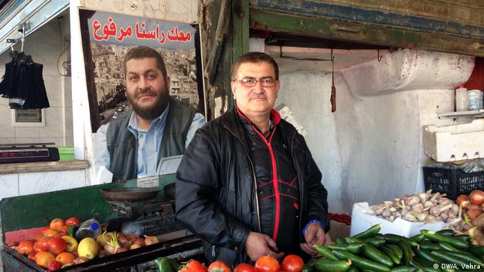 A vendor stands in front of his wares - vegetables - and a life-size poster of Ziad Allouki in the Tripoli souk