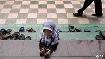 An Indonesian girl waits for her parents outside a mosque in Jakarta