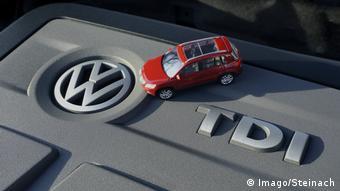 Двигатель TDI, эмблема Фольксваген и модель красного автомобиля