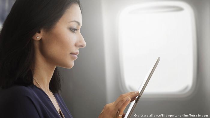 Junge Frau, die Tablet im Flugzeug verwendet (picture alliance/Bildagentur-online/Tetra Images)