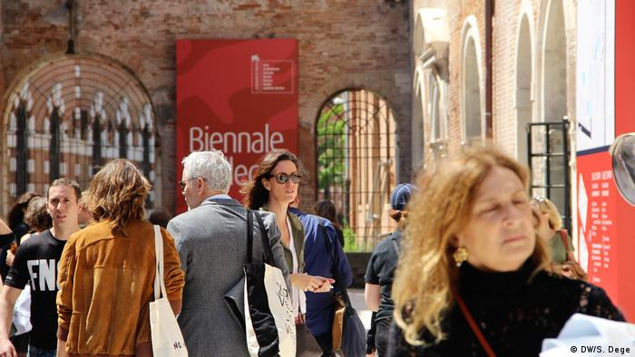 people with a Biennale poster in the background (DW/S. Dege)
