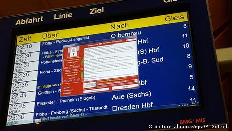 Компьютерное окно с требованием хакеров о выкупе поверх табло с расписанием поездов в Германии