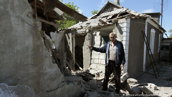 A man by a yard of a residential house wrecked by a shelling of Dokuchaievsk, Donetsk Region