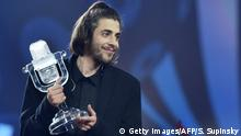 13.05.2017 Portuguese singer representing Portugal with the song Amar Pelos Dios Salvador Vilar Braamcamp Sobral aka Salvador Sobral holds the trophy as he celebrates on stage after winning during the final of the 62nd edition of the Eurovision Song Contest 2017 Grand Final at the International Exhibition Centre in Kiev, on May 13, 2017. / AFP PHOTO / Sergei SUPINSKY (Photo credit should read SERGEI SUPINSKY/AFP/Getty Images)