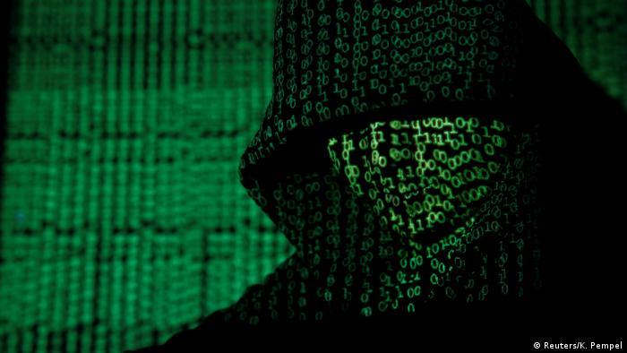 Symbolbild Cyberkriminalität: Computercode wird auf einen Mann mit Kapuze projiziert