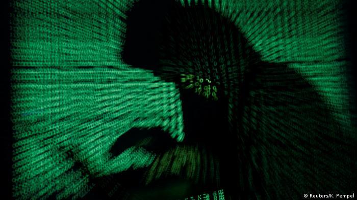 Черная тень человека с ноутбуком в руках на фоне зеленых знаков программного кода