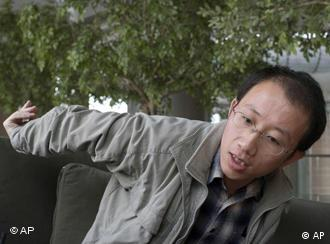**FILE** In this March 31, 2006 file photo, Chinese activist Hu Jia demonstrates how he was physically detained by police officers during an interview at a cafe in Beijing, China._ The European Parliament gave a jailed Chinese dissident a one-minute standing ovation on Wednesday as it honored him in absentia with its top human rights award. Hu Jia, who chronicled the harassment of other activists in China before getting sentenced to 3 1/2 years in jail last April, was named winner of the 2008 Sakharov Prize. (AP Photo/Ng Han Guan)