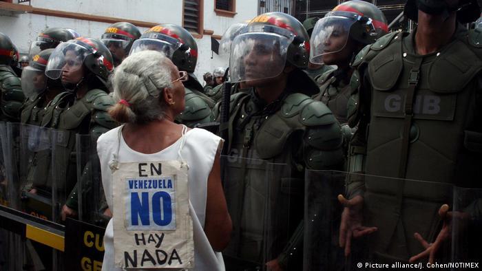 Protesta silenciosa y pacífica. Una mujer mayor en Caracas mira a los ojos a una Guardia Nacional.