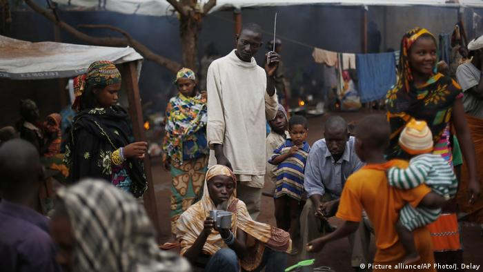 Men, women and children sitting and standing in a group around a radio (Picture alliance/AP Photo/J. Delay)