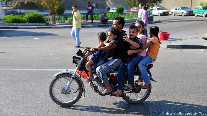 رجل مع أطفاله على دراجة نارية في الطريق إلى مظاهرة ضد الرئيس الأسبق محمد مرسي