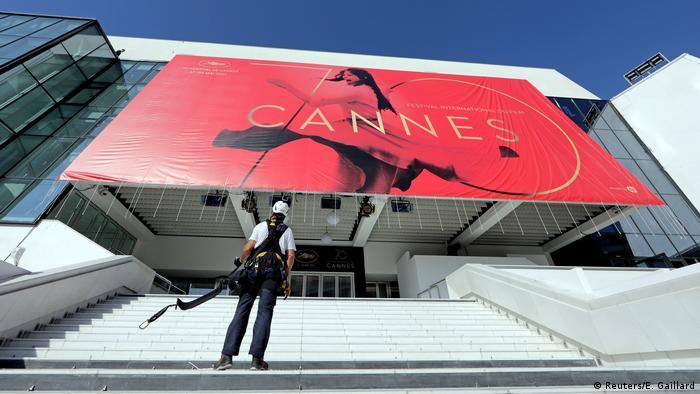 Filmfestival Cannes Plakat 2017 mit Fotograf im Vordergrund (Foto: Reuters/E. Gaillard)