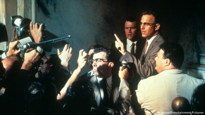 Filmstill JFK: Gerichtsszene mit Reportern und Anwalt und vielen Menschen