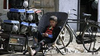 An Afghan boy waits for customers at a generator shop in Kabul