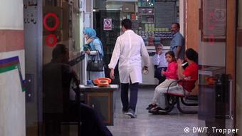People walk and wait in a hallway in a Jewish hospital in Tehran