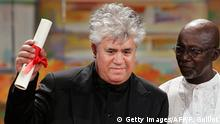 ARCHIV 2006****Cannes, FRANCE: Spanish director Pedro Almodovar celebrates on stage next to Malian director Souleymane Cisse after winning the Best Screenplay award for 'Volver' during the closing ceremony of the 58th edition of the Cannes International Film Festival on the French Riviera, 28 May 2006. British director Ken Loach won the Cannes film festival's top prize, the Palme d'Or, for his movie The Wind That Shakes the Barley, which recounts Ireland's early struggle for independence. Loach, who turns 70 next month, has described the film as also being a critique of the US-led war on Iraq, with guerrillas seeking to oust an occupying military force. AFP PHOTO / FRANCOIS GUILLOT (Photo credit should read FRANCOIS GUILLOT/AFP/Getty Images)