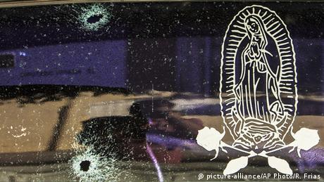 Foto de una ventana con dos hoyos de bala y una calcomanía de la Virgen de Guadalupe