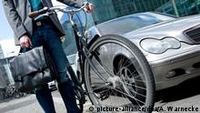 ILLUSTRATION - Ein Mann schiebt am 23.05.2013 an einer Straße in Berlin sein Fahrrad neben einem Auto, während er eine Aktentasche in der Hand hält. | Verwendung weltweit