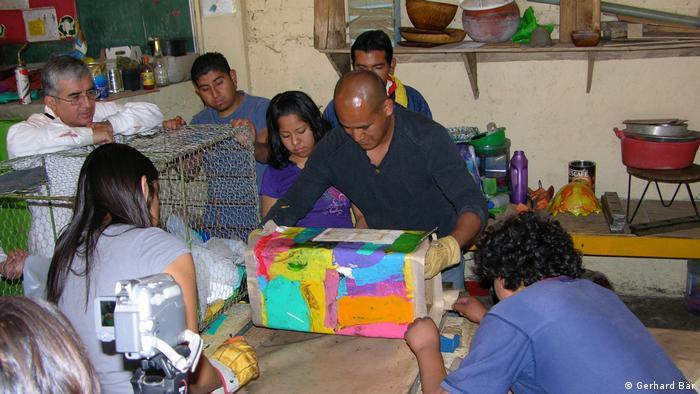 Un grupo de jóvenes mexicanos observa como una persona moldea un bote de polietileno reciclado.