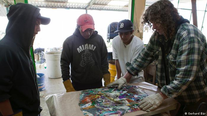 Habitantes de la colonia Miravalle observan cómo el artista Gerhard Bär funde el plástico con planchas de calor.