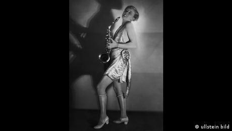 Σαξόφωνο, φανταχτερά φορέματα και νάιλον κάλτσες – η ηθοποιός Χέρτα Σρέτερ σε ένα μπαλ μασκέ. Η φωτογραφία αυτή δημοσιεύθηκε στην «Berliner Illustrirte Zeitung» το 1928. Μόλις μερικά χρόνια αργότερα τέτοιες λήψεις ήταν αδιανόητες. Με την ανάληψη της εξουσίας από τους Ναζί, η τζαζ μουσική θεωρήθηκε «εκφυλισμένη» και οι δυναμικές γυναίκες δεν είχαν ρόλο στις θεατρικές σκηνές.