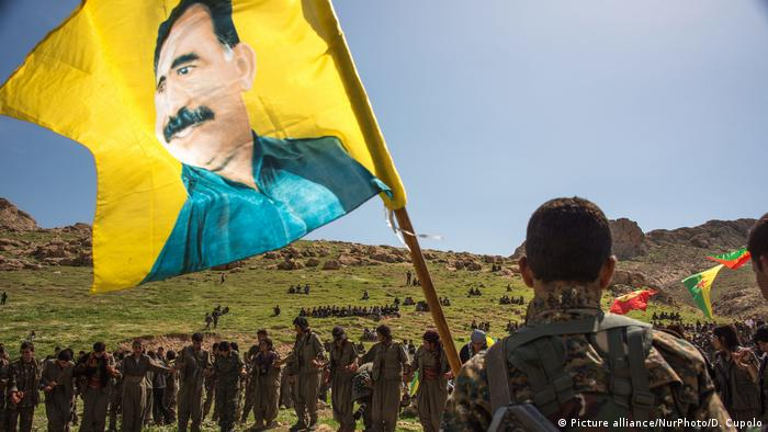 Kurdish militias carry a flag of PKK founder Abdullah Ocalan (Picture alliance/NurPhoto/D. Cupolo)