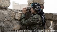 Sept. 28, 2014 - Rabia, Ninewa Governorate, Iraq - 28/09/2014. Rabia, Iraq. A female fighter belonging to the Syrian-Kurdish YPJ scans Islamic State territory from a YPG position in the Iraqi border town of Rabia...Facing each other across the Iraq-Syria border, the towns of Al-Yarubiyah, Syria, and Rabia, Iraq, were taken by Islamic State insurgents in August 2014. Since then The town of Al-Yarubiyah and parts of Rabia have been re-taken by fighters from the Syrian Kurdish YPG. At present the situation in the towns is static, but with large exchanges of sniper and heavy machine gun fire as well as mortars and rocket propelled grenades, recently occasional close quarter fighting has taken place as either side tests the defences of the other |