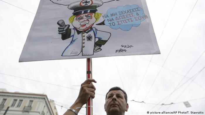 An anti-austerity protester in Greece in 2017 holds a placard with a cartoon of an a neo-Nazi Chancellor Angela Merkel that reads: Don't forget to give up your home, too.
