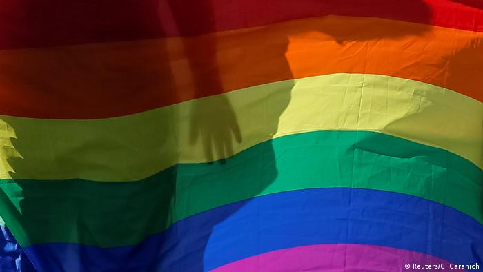 The silhouette of a person is seen behind an LGBT flag