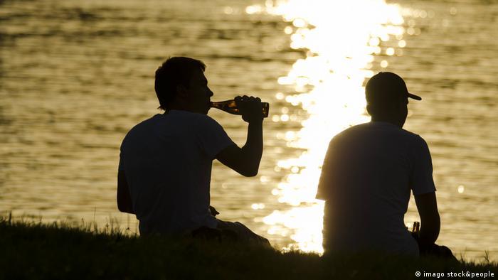 Silhuetas de dois rapazes ao pôr-do-sol, à beira d'água, um deles bebe de uma garrafa