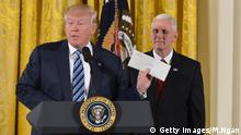 US President Donald Trump holds the letter left for him by former US President Barack Obama, as Vice President Mike Pence watches, before the swearing in of the White House senior staff at the White House on January 22, 2017, in Washington, DC. / AFP / MANDEL NGAN (Photo credit should read MANDEL NGAN/AFP/Getty Images)