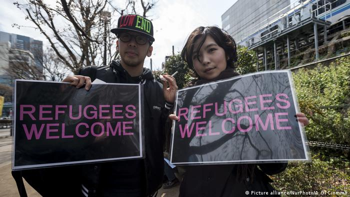 Protesters holding signs saying 'Refugees welcome'